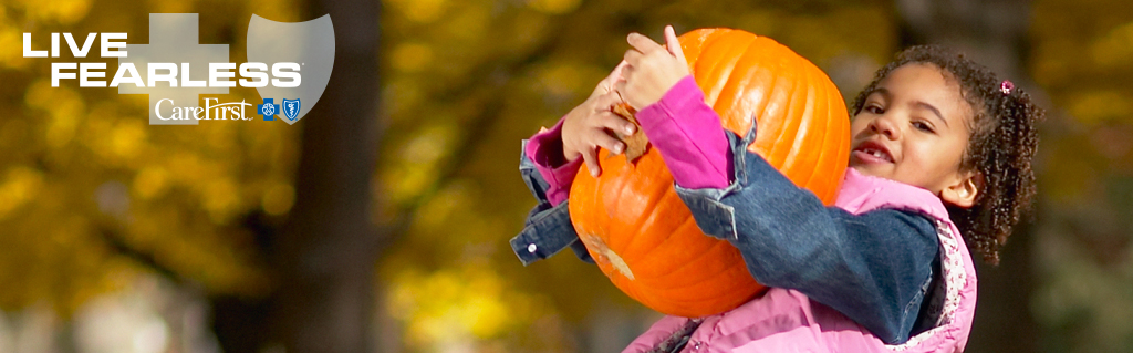 Young girl holding heavy pumpkin